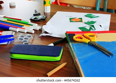 Lots of different arts and craft supplies on a wooden table: pencil, felt tips, three scissors, cutted paper, stapel of colored paper and a bag of plastic eyes.