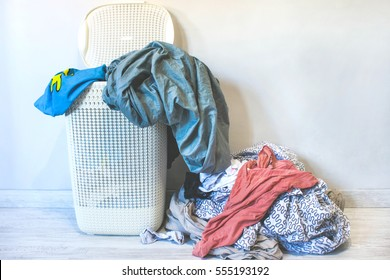 Lots of dirty linen on the floor and a full Laundry basket
