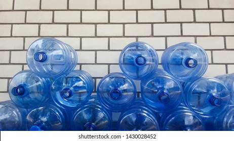 Lots of empty five-gallon blue plastic water bottles stacked on White brick wall.