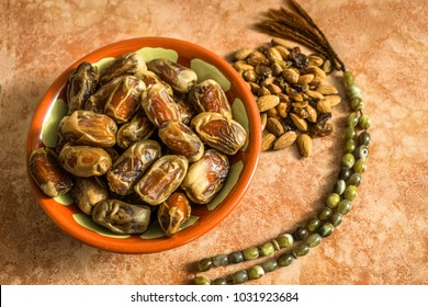lots of fresh and healthy dates kept in a muddy Arabian traditional pot and almonds and a religious Tasbeeh  kept of a marble table and ready to break fast in the holy month of Ramadan