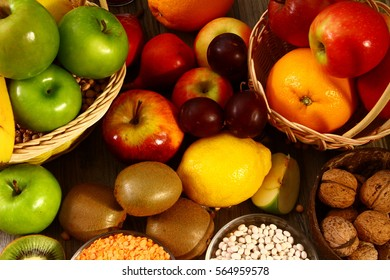 A lots of fruits (kiwi, green and red apples, lemon), walnuts and pulse, may be used as a background or as a concept of healthy food