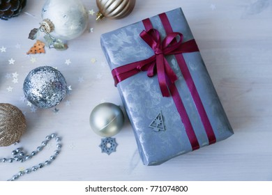 Lots of gift boxes on white wood background. Stylish modern presents in gray and green paper. Christmas and winter holidays concept, top view, flat lay