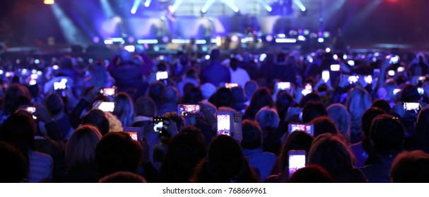 lots of gilrs and guys with the smartphone turned on to record or take pictures during the live concert