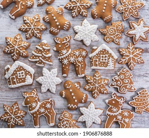 Lots of gingerbread cookies in different shapes with a pattern of white icing on a wooden surface. Top view