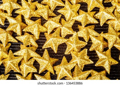 Lots of golden sparkling five pointed stars on black glass. These are glittering with shiny golden color.