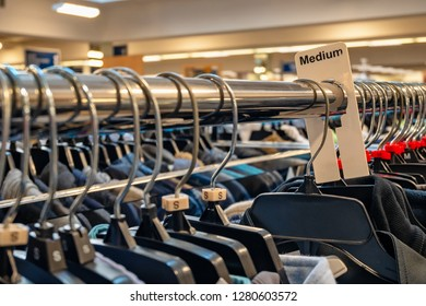 Lots of hangers on a shelf, selective focus on Medium size label.