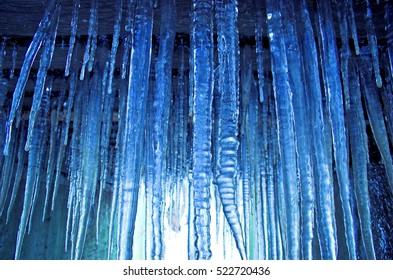 Lots of icicles hanging under a small bridge.