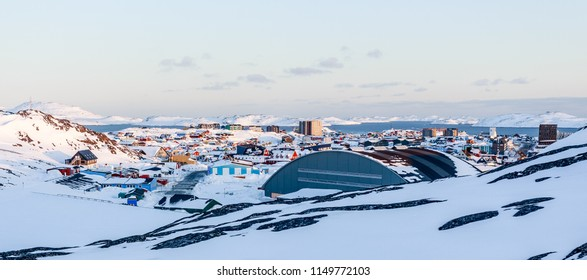 Lots of Inuit houses scattered on the hill in Nuuk city covered in snow with sea fjord and mountains in the background, Greenland