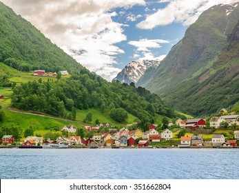 A lots of little colorful traditional Norwegian houses near the sea with green forest on mountains on background and blue sky with dark clouds, Sognefjord, Norwa