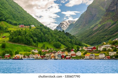 A lots of little colorful traditional Norwegian houses near the sea with green forest on mountains on background and blue sky with dark clouds, Sognefjord, Norway