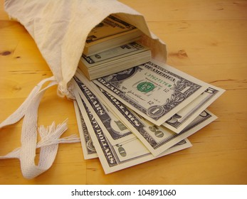 Lots of Money Flowing from a Canvas Money Bag