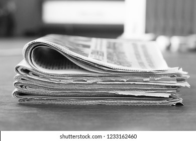 Lots of newspapers folded and stacked in one pile. Stack of old journals concept for communication. Pages with news on wooden table for background. Side view, selective focus