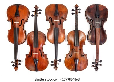 Lots of old, handmade violins on white background