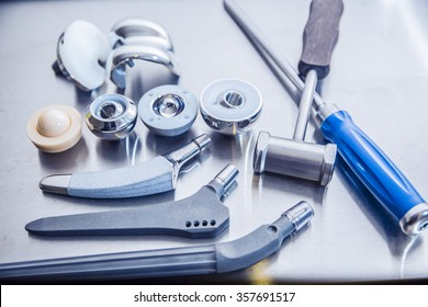 lots of parts for transplantation of leg joints and tools for surgical operations on replacement  lie against a metal surface