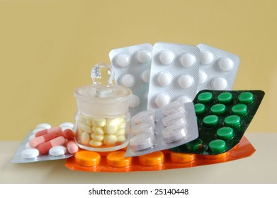 Lots of pills in their containers on yellow background