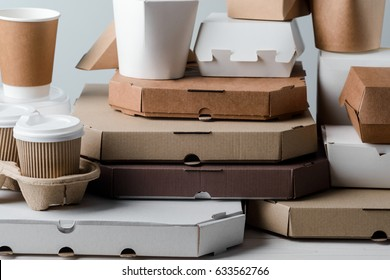 Lots of pizza boxes, take-out coffee cups and microwaveable paper food containers, close-up. Neutral background. Binge eating, food delivery.
