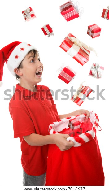Lots of presents fall into a young  boys Christmas sack to his delight.  Some motion visible in presents.