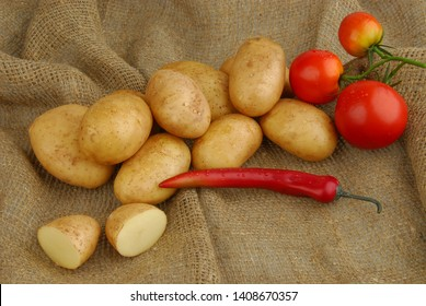 Lots of raw potatoes on sackcloth with tomatoes and pepper on gray isolated background