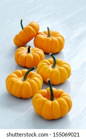 Lots of small pumpkins on a white surface