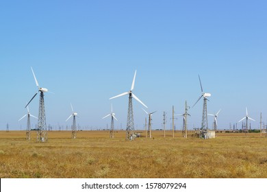 Lots of spinning wind turbines against a clear blue sky. Ground for alternative energy in the Crimea. Wind farm