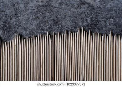 Lots of toothpicks on dark grey table as background. Many toothpicks on grunge background. Stack of wooden sticks.