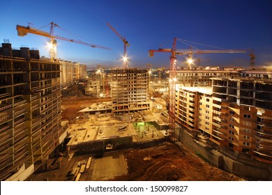 Lots of tower cranes build large residential buildings at night.