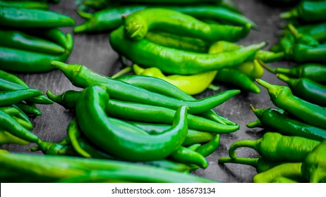 Lots of vivid acid green peppery hot pepperonies  on wooden table on the marketplace