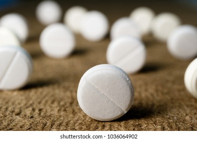 lots of white round medical pills on brown background scattered