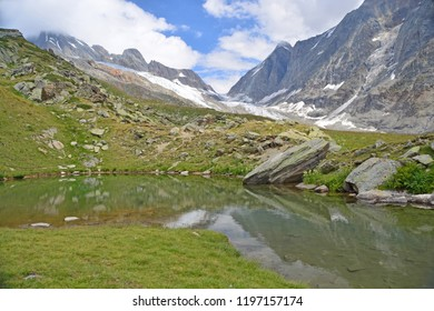 The Lotschenlucke Pass with the Hollandia Hut above it. In the foreground the Annensee pool.  In the Swiss Bernese Alps