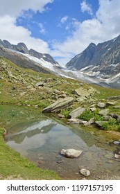 The Lotschenlucke Pass with the Hollandia Hut above it. In the foreground the Annensee pool. In the Bernese Alps, Switzerland