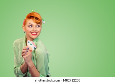Lottery win. Closeup red head beautiful young woman pretty happy smiling pinup girl button shirt holding euro money and smiling looking to the side daydreaming, retro vintage 50's hairstyle over green