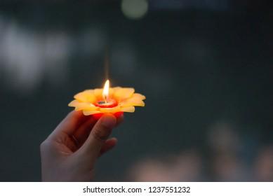 Lotus candle in woman hand in Loy Krathong festival. Environmental friendly Krathong.