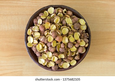 Lotus seed (Lotus nut) with husk in clay bowl, top view on wood background