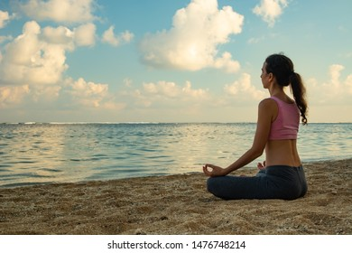 Lotus yoga pose. Yoga at the beach. Young woman sitting on sand, meditating, practicing yoga and pranayama with gyan mudra at the beach. Sunset time. Yoga retreat in Bali, Indonesia.