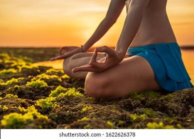 Lotus yoga pose. Close up gyan mudra. Focus on one hand. Yoga at the beach. Young woman meditating, practicing yoga and pranayama with gyan mudra. Sunset time golden hour. Yoga lifestyle. Bali