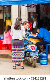 LOUANGPHABANG, LAOS - JANUARY 11, 2017: Women with a motorcycle on a city street. Vertical