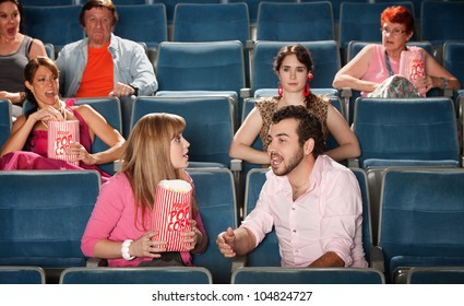 Loud couple talking with annoyed people in crowded theater