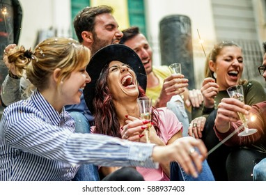Loud happy friends making party with champagne,confetti and sparklers outdoor - Young people celebrating birthday drinking and laughing - Fest concept - Focus on center girl with hat - Unfiltered