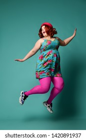 Loud laughing plus-size lady overweight woman in funny hat and sundress jumps funny or flying away from something on mint background