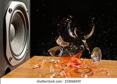 Loud Music Can Cause Damage - Studio Shot of Glass of wine exploding in front of a loud Subwoofer