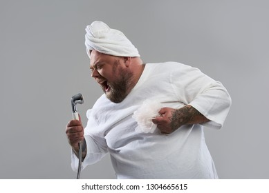 Loud song. Bearded fat man closing his eyes and using a shower head as a microphone while singing