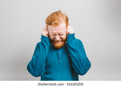 Too loud sound. Furious young bearded man covering ears with hands and keeping eyes closed while standing against grey background