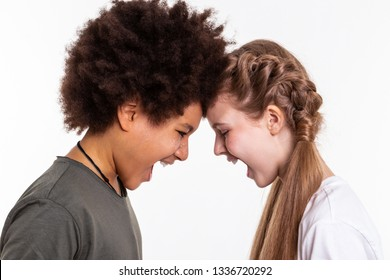 Loudly yelling. Aggressive good-looking children releasing emotions on each other while connecting foreheads and opening mouths