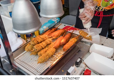 Loudon, TN / USA - SEPTEMBER 28 2019: FRIED PICKLE FESTIVAL Fried pickle swirls and corn dogs under a heat lamp in a food booth at the festival.