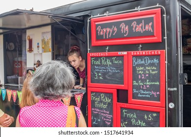 Loudon, TN / USA - SEPTEMBER 28 2019: FRIED PICKLE FESTIVAL Food truck selling fried pickle tacos with customers ordering from the red and black menus