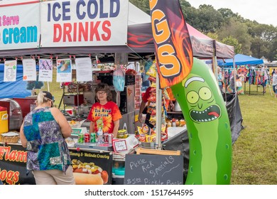 Loudon, TN / USA - SEPTEMBER 28 2019: FRIED PICKLE FESTIVAL Inflatable pickle with crazy face in front food vendor at the festival