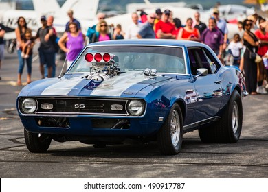 LOUDOUN COUNTY, VIRGINIA - 24 SEPTEMBER 2016: A modified classic Camaro drives past a group of onlookers