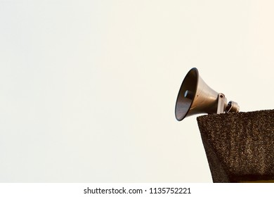 Loudspeaker or broadcast speaker on the rooftop of a building with the golden sunlight.