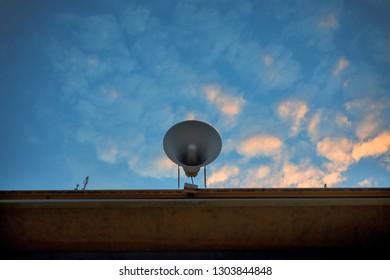 loudspeaker on building roof against beautiful morning colorful sky