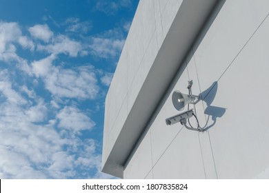 Loudspeakers and CCTV security cameras observation on a wall of a building